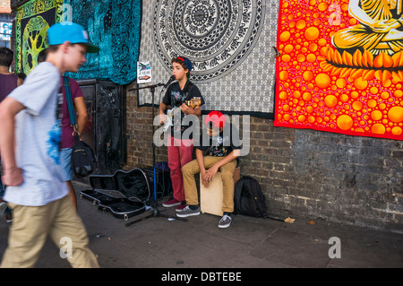 Two young boy buskers performing live music in the street near Camden Market, London, England, UK. - Stock Photo