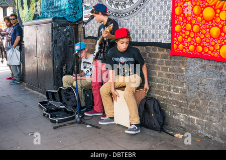 Three young boy buskers performing live music in the street near Camden Market, London, England, UK. - Stock Photo