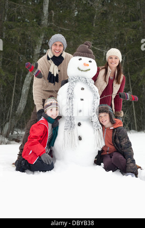 Portrait of happy family with snowman - Stock Photo