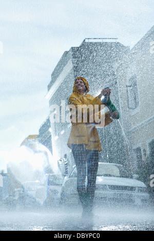 Happy woman walking barefoot in rain - Stock Photo