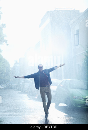 Happy man with arms outstretched in rainy street - Stock Photo