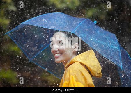 Happy woman with umbrella in rain - Stock Photo