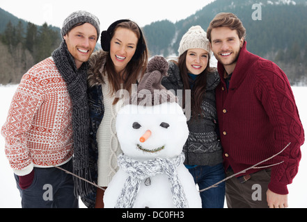 Portrait of happy friends with snowman - Stock Photo