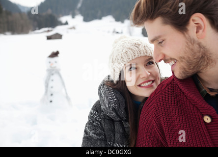 Close up of happy couple in snowy field with snowman - Stock Photo