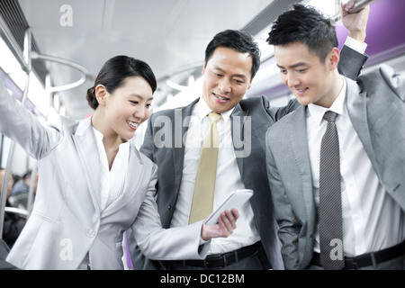 Cheerful business persons with mobile phone in subway train - Stock Photo