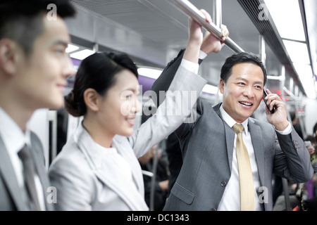 Cheerful business persons in subway train - Stock Photo