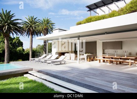 Lounge chairs on deck of modern house - Stock Photo