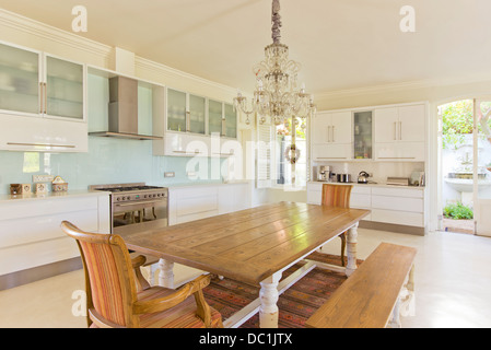 Chandelier over wooden table in kitchen - Stock Photo