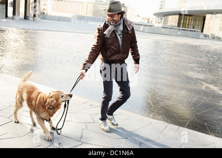 Mid adult man pulling leash on pet dog in city - Stock Photo