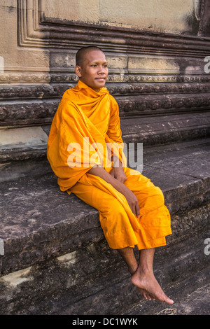Young Buddhist monk sitting at temple in Angkor Wat, Siem Reap, Cambodia - Stock Photo