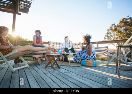 Young friends sitting together on balcony - Stock Photo