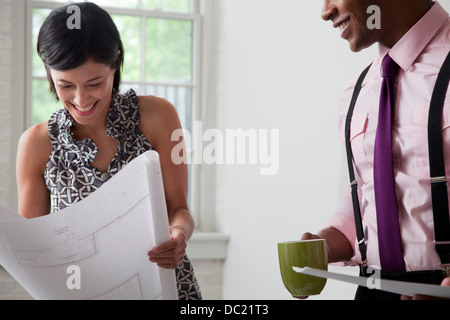 Office colleagues holding blueprints in office, smiling - Stock Photo