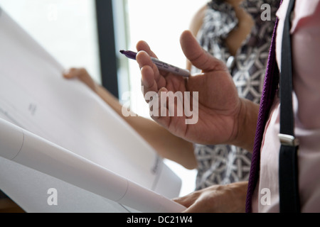 Office colleagues holding plans in meeting, close up - Stock Photo