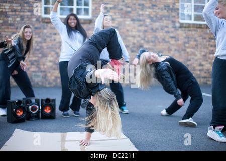 Blond girl breakdancing in playground - Stock Photo