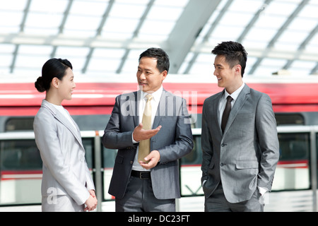 Chinese business persons talking at subway station - Stock Photo