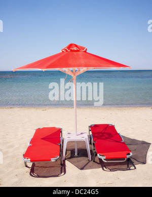 Orange red sun beds and umbrella on the sandy beach in Greece with blue sea - Stock Photo