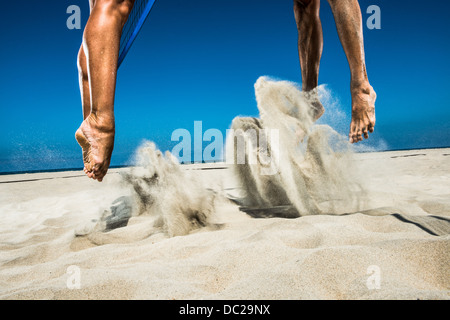 Two beach volleyball players jumping mid air in sand - Stock Photo