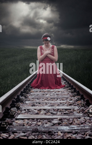 a girl in a red dress is sitting on railway tracks - Stock Photo