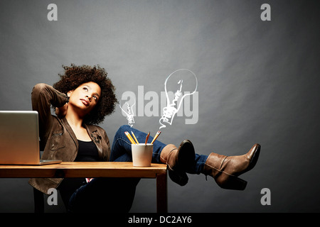 Woman with legs on table searching for ideas - Stock Photo