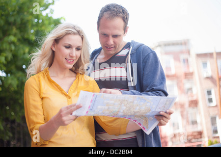 Couple reading map - Stock Photo