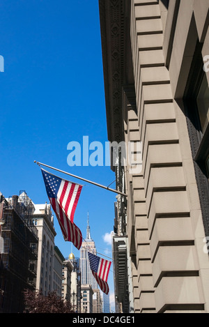 The Empire State Building with two American flags - Stock Photo