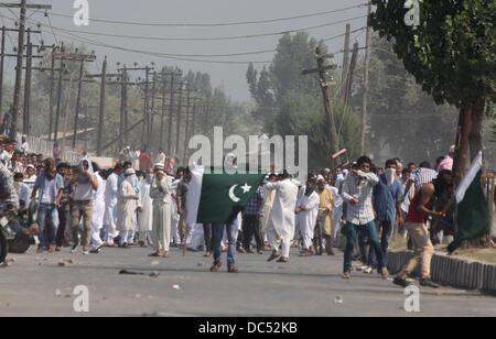 Srinagar, Kashmir, India. 09th Aug, 2013. Kashmiri Muslim protester holds pakistani flag during a clash between - Stock Photo