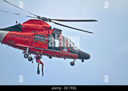 A US Coast Guard rescue swimmer is hoisted down from a HH-65C Dolphin helicopter during a training exercise August - Stock Photo