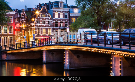 Halvemaans bridge from Amsterdam, illuminated, with typical dutch houses in the background - Stock Photo