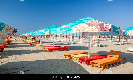 Row of colorful seabeds and umbrellas on a sandy beach - Stock Photo