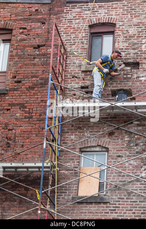 A brick mason works on a scaffolding three stories high to repair a brick wall in St. John, Nova Scotia, Canada. - Stock Photo