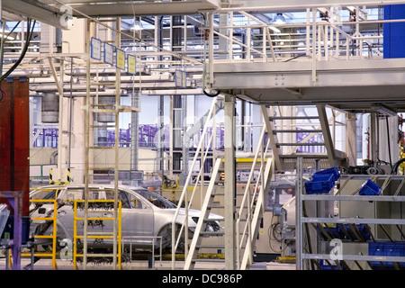 cars in a row on conveyor at car plant - Stock Photo
