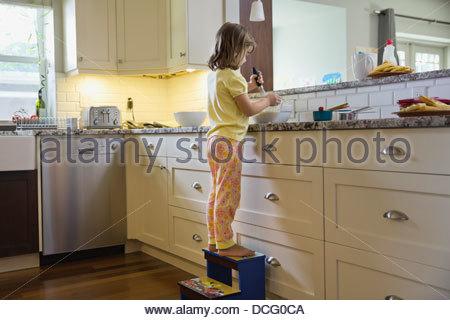 Little girl mixing waffle batter - Stock Photo