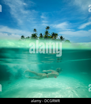 Woman snorkeling in a tropical lagoon - Stock Photo