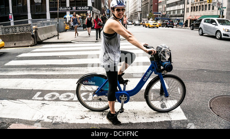 smiling young woman on bicycle from Citibike bike sharing system rides in bicycle lane at Park Avenue South & 34th - Stock Photo