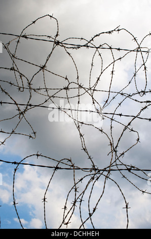 Tangled barbed wire fence against a dramatic sky background - Stock Photo
