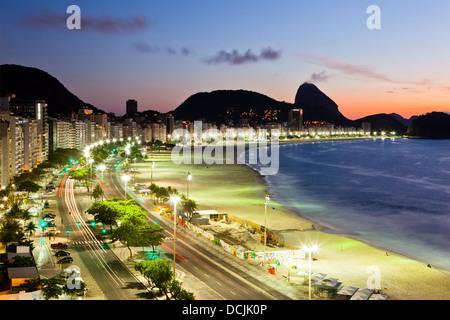 Sunrise at Copacabana beach, Rio de Janeiro, Brazil. Atlantica avenue, Sugar Loaf mountain in background. - Stock Photo