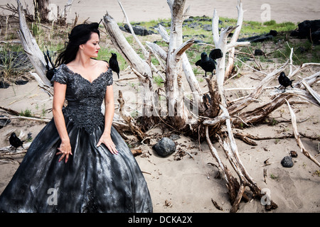 A black haired woman in a black wedding gown surrounded by crows - Stock Photo