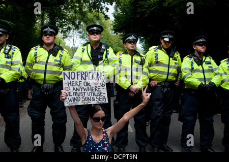Site of Cuadrilla drilling. Demonstration against fracking . A demonstrator sits down in front of a line of police. - Stock Photo