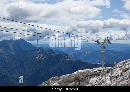 empty chairlifts in Julian Alps, Slovenia - Stock Photo