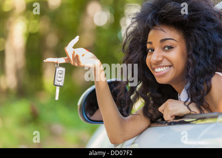 Young beautiful black teenage driver holding car keys driving her new car - Stock Photo