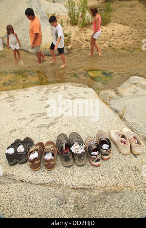 A Family Leaves Their Shoes On The Shore And Walks In The Shallow Water At The Sierra La Laguna Biosphere Reserve; - Stock Photo