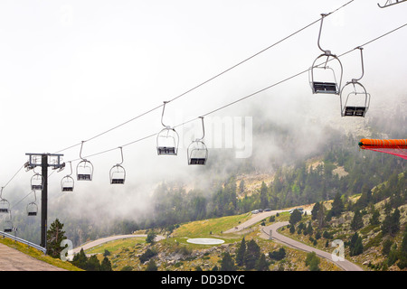 chairlifts with fog on the mountains Vallter 2000 ski resort in the Pyrenees of Girona, Catalonia (Spain) - Stock Photo