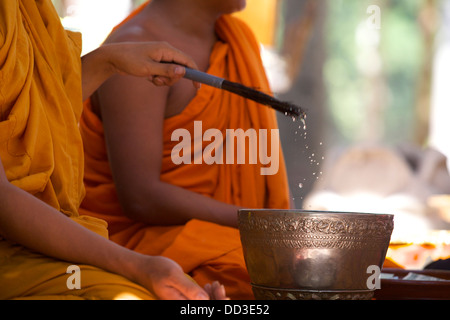 Buddhist monks in blessing ceremony at Bayon Temple, Angkor Thom, Cambodia - Stock Photo