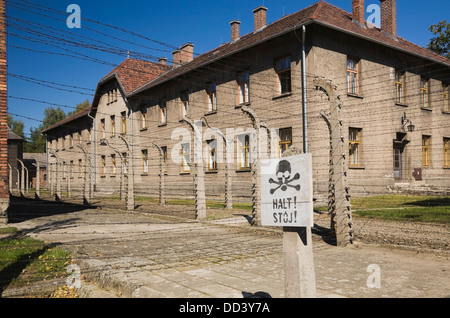 Warning Sign In Front Of A Barb Wire Fence And Building Inside The Auschwitz I Former Nazi Concentration Camp; Auschwitz, - Stock Photo