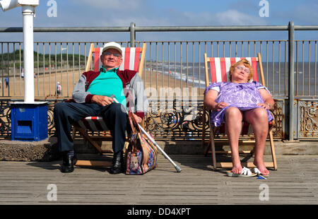 Skegness, Lincolnshire, UK. 26th Aug, 2013. Couple enjoy the sunshine while relaxing on Skegness pier. Credit:  - Stock Photo