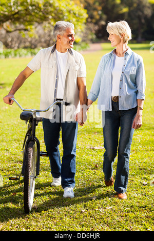 beautiful senior couple walking a bike in park holding hands - Stock Photo