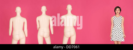 Conceptual portrait of young serious multiracial woman standing alone, left out from a group of mannequins - Stock Photo