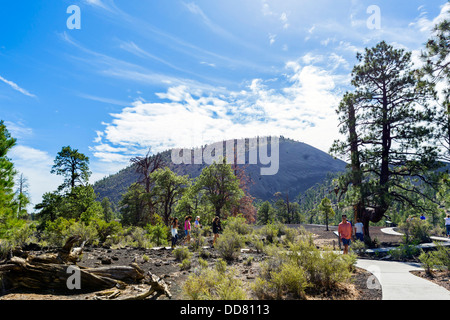 Tourists on the Lava Flow Trail at Sunset Crater Volcano National Monument, near Flagstaff, Arizona, USA - Stock Photo
