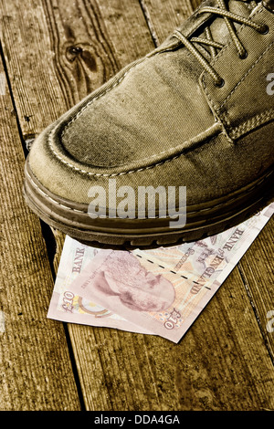 Shoe on top of two English sterling 10 pound notes - Stock Photo