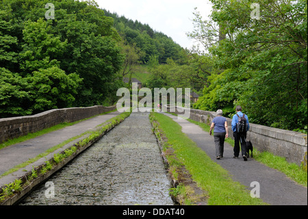 A senior couple walking a dog along the Cromford canal Derbyshire England uk - Stock Photo